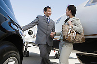 Mid-adult Asian businesswoman and businessman flirting outside of car and airplane.