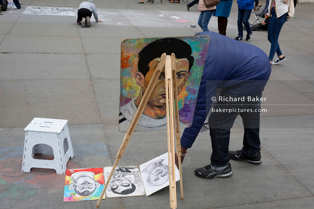 A caricature street artist lays out his portrait examples on the pavement in Trafalgar Square, on 2nd May 2019, in London, England.