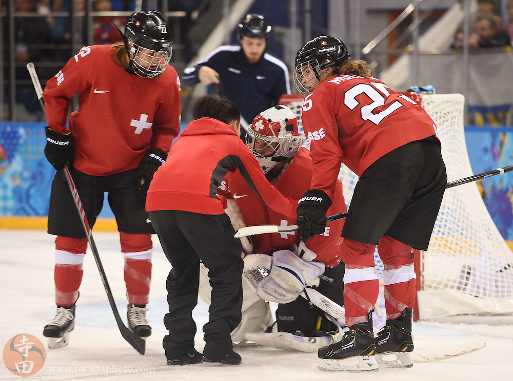 Feb 15, 2014; Sochi, RUSSIA; Switzerland goalkeeper Florence Schelling (41) is looked at by a trainer following a collision in a women's quarterfinals ice hockey game during the Sochi 2014 Olympic Winter Games at Shayba Arena.
