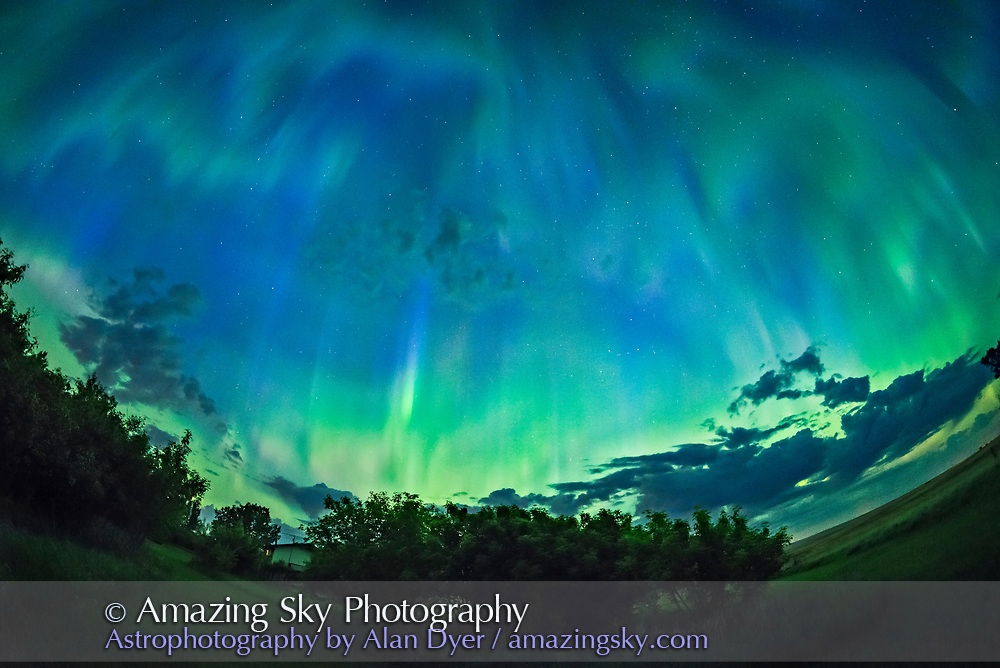 The great all-sky aurora of the night of May 27/28, 2017, shot from home in southern Alberta looking north toward the auroral oval. The brightest curtain is fringed with pink from glowing nitrogen. Above, the aurora is exhibiting a typical post-substorm patchiness and pulsating, with patches of green ad blue covering the sky. With the oncoming morning twilight, the sky and aurora is beginning to look more blue. The Big Dipper is at left. Notice the sharp-edged dark bands at upper right. Dark aurora?<br /><br />This is a stack of 8 exposures for the ground to smooth noise, and one exposure for the sky, all 1.6-second exposures at f/2.8 with the 12mm Rokinon full-frame fish-eye lens and Nikon D750 at ISO 3200. Shot as part of a time-lapse sequence.