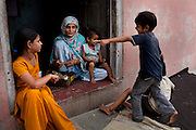 Nafeesa, 27, rolls bidis (indian cigarettes) as her 4 children aged 10, 7, 4, and 1.5 years, play in her house compound in a slum in Tonk, Rajasthan, India, on 19th June 2012. Nafeesa's health deteriorated from bad birth spacing and over-working. While her husband works far from home, she rolls bidis to make an income and support the family. She single-handedly runs the household and this has taken a toll on her health and financial insufficiencies has affected her children's health. Photo by Suzanne Lee for Save The Children UK