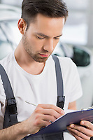 Male automobile mechanic writing on clipboard in workshop