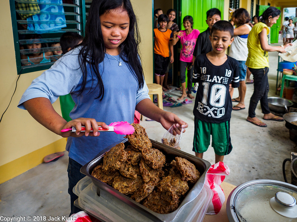 24 JANUARY 2018 - LIGAO, ALBAY, PHILIPPINES: MARIA MIRA CAPIL, an evacuee from a community near the Mayon volcano, fries banana blossoms in the hallway of the school she is temporarily living in in Ligao with 1,849 other people from the volcano. The Mayon volcano continued to erupt Tuesday night and Wednesday forcing the Albay provincial government to order more evacuations. By Wednesday evening (Philippine time) more than 60,000 people had been evacuated from communities around the volcano to shelters outside of the 8 kilometer danger zone. Additionally, ash falls continued to disrupt life beyond the danger zones. Several airports in the region, including the airport in Legazpi, the busiest airport in the region, are closed indefinitely because of the amount of ash the volcano has thrown into the air.    PHOTO BY JACK KURTZ