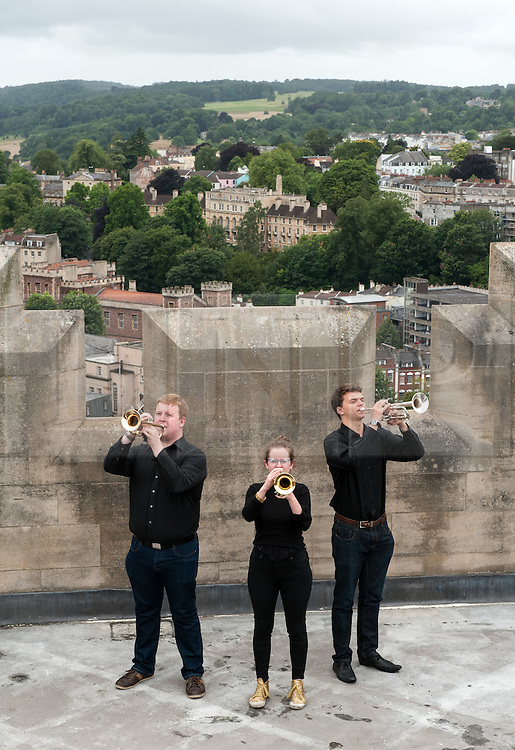 """© Licensed to London News Pictures. 27/07/2015. Bristol, UK.  """"Fanfare for Bristol"""", titled """"At the Top of the Tide"""", composed by David Mitcham, commissioned by Bristol Proms 2015.  Picture shows trumpeters l-r: Chris Hart, Helen Whitemore, Gideon Brooks, playing at the top of the Wills Memorial Bell Tower.  The fanfare was performed live for the Mayor of Bristol, George Ferguson and Artistic Director of the Bristol Old Vic, Tom Morris for the first time at Bristol's famous Temple Mead train station, heralding the opening of the Bristol Proms 2015.  David Mitcham's  """"At the Top of the Tide"""" was inspired by 'Bristol's inextricable links to the sea'.  The first performance by Arc Brass took place outside the Engine Shed, and throughout the day, performances took place at the Watershed, Pero's Bridge, the Wills Memorial Bell Tower and finally at Bristol Old Vic itself. David Mitcham, who has worked extensively for the BBC Natural History Unit based in Bristol said: """"I am thrilled that my Fanfare """"At the Top of the Tide"""" has been chosen for the city of Bristol and to open Bristol Proms 2015. I hope the Fanfare represents the rich diversity of Bristol, its maritime and industrial heritage as well as being a celebration of the spirit of the city and the energy it will carry into the future.""""  Bristol Proms 2015 runs from today, 27th July to 1st August and features some of the world's finest musicians including Alison Balsom, Miloš Karadaglić, Pumeza Matshikiza and Daniel Hope.  Photo credit : Simon Chapman/LNP"""