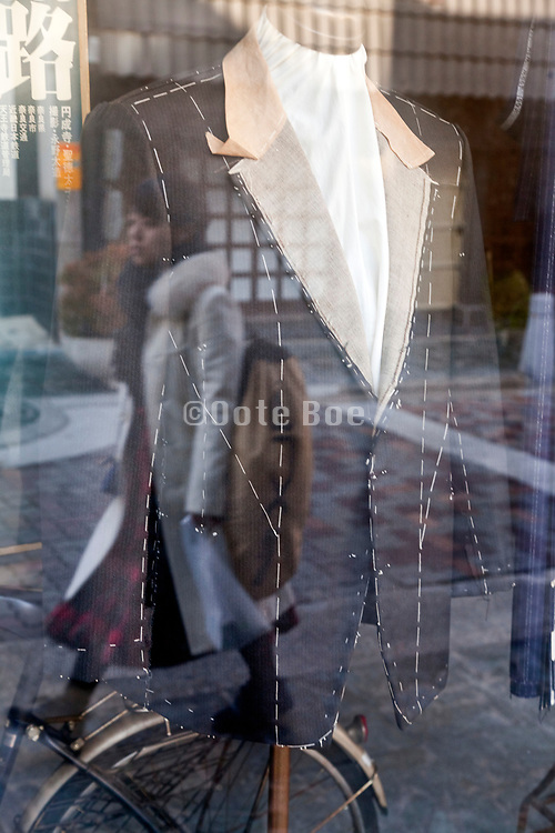 tailors custom made jacket display with woman walking by in the window reflection Nara Japan
