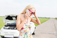 Worried woman using mobile phone on country road with broken down car in background
