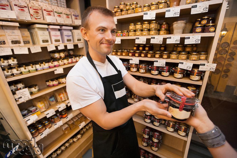 Salesman giving jar of jam to female customer in grocery store