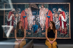 "© Licensed to London News Pictures. 22/10/2018. LONDON, UK. A staff member sits next to ""The Adoration of the Magi"", 1894, by Edward Burne-Jones.  Preview of the largest Edward Burne-Jones retrospective to be held in a generation at Tate Britain.  Burne-Jones was a pioneer of the symbolist movement and the only Pre-Raphaelite to achieve world-wide recognition in his lifetime.  The exhibition runs 24 October to 24 February 2019.  Photo credit: Stephen Chung/LNP"