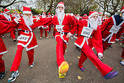 The pre run warm up for The London Santa Run, a 6k festive charity fun run, with around 2,000 Santa's. It  is organised to raise funds for Disability Snowsport UK, a national charity helping people with disabilities to access the thrill of snowsports. Battersea Park, London, UK.