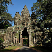 This gateway lies between Angkor Wat and Angkor Thom, two of the most visited sites in the Angkor temple complex.<br /> <br /> Angkor Wat (Khmer: អង្គរវត្ត) was first a Hindu, later a Buddhist, temple complex in Cambodia and the largest religious monument in the world. The temple was built by the Khmer King Suryavarman II in the early 12th century in Yaśodharapura (Khmer: យសោធរបុរៈ, present-day Angkor), the capital of the Khmer Empire, as his state temple and eventual mausoleum. Breaking from the Shaiva tradition of previous kings, Angkor Wat was instead dedicated to Vishnu. As the best-preserved temple at the site, it is the only one to have remained a significant religious center since its foundation. The temple is at the top of the high classical style of Khmer architecture. It has become a symbol of Cambodia, appearing on its national flag, and it is the country's prime attraction for visitors.<br /> <br /> Angkor Wat combines two basic plans of Khmer temple architecture: the temple-mountain and the later galleried temple, based on early Dravidian architecture, with key features such as the Jagati. It is designed to represent Mount Meru, home of the devas in Hindu mythology: within a moat and an outer wall 3.6 kilometres (2.2 mi) long are three rectangular galleries, each raised above the next. At the centre of the temple stands a quincunx of towers. Unlike most Angkorian temples, Angkor Wat is oriented to the west; scholars are divided as to the significance of this. The temple is admired for the grandeur and harmony of the architecture, its extensive bas-reliefs, and for the numerous devatas adorning its walls.<br /> <br /> The modern name, Angkor Wat, means &quot;Temple City&quot; or &quot;City of Temples&quot; in Khmer; Angkor, meaning &quot;city&quot; or &quot;capital city&quot;, is a vernacular form of the word nokor (នគរ), which comes from the Sanskrit word nagara (नगर). Wat is the Khmer word for &quot;temple grounds&quot; (Sanskrit: वाट vāṭa &quot;&quot;
