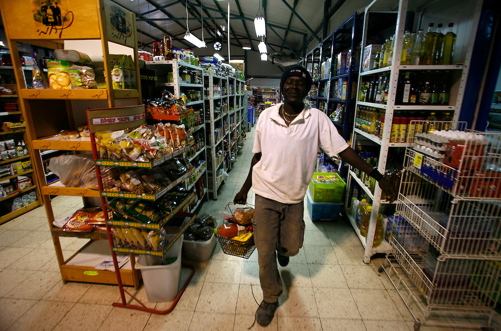 Mohammad Adam Hater 26 refugee from Darfur buy grocery in Kibbutz Urim in Israel at Wednesday November 14.2007......Mohammad born in Darfur and run away from Darfur after his village was burn down and most of the people were dead... He run away to Khartoum and from there to Egypt, in Egypt he didn?t got a refugee papers from the UN. He say it hard to be in Egypt with no papers so he keep his journey to Israel crossing the Sinai desert, wean he pass illegally the border to Israel, the Israeli army got him and put him in detention camp and then he  got to Kibbutz Urim a year and three month ago, Kibbutz Urim voluntary to adopt refugees from Darfur and give them work place to stay and all they needs ..Today one of the family?s in the Kibbutz are taking care of him and he work in irrigation for 10 -12 hours a day with Israeli kibbutz member named Oz Gang..Mohammad say he is happy in Israel and I have food place to sleep and food and no one is stopping him from travel in Israel, but he still didn?t get refugee status from the UN. And because of that he is not filling free...He didn?t have news from his family for three years and he doesn?t know if there are lives or dead. ..