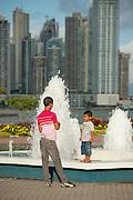 Young man and kid at fountain. Cinta Costera bayside road, Panama City, Panama, Central America.