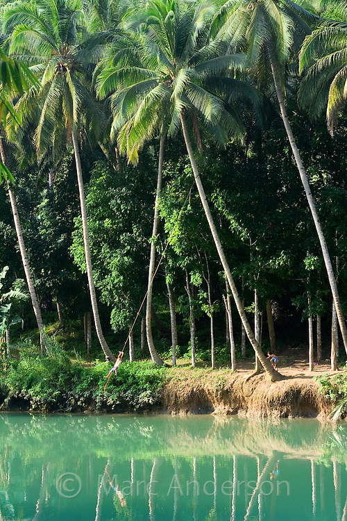 A boy swinging on a rope over the Loboc River, Bohol, Philippines...