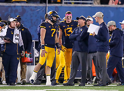 Oct 25, 2018; Morgantown, WV, USA; West Virginia Mountaineers head coach Dana Holgorsen talks with West Virginia Mountaineers quarterback Will Grier (7) and West Virginia Mountaineers wide receiver David Sills V (13) during the third quarter against the Baylor Bears at Mountaineer Field at Milan Puskar Stadium. Mandatory Credit: Ben Queen-USA TODAY Sports