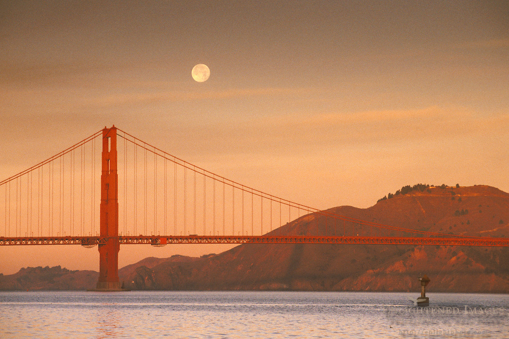Full moon setting over the North Tower of the Golden Gate Bridge at dawn, San Francisco Bay, California