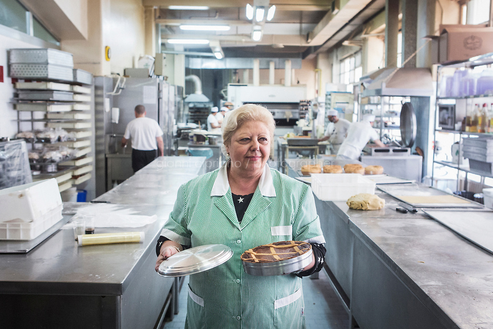 NAPLES, ITALY - 11 APRIL 2017: Anna, a patissier and packaging manager at Scaturchio, a historic bakery and pastry shop founded in 1905, shows a freshly baked Neapolitan Pastiera ready to be shipped to a customer, in Naples, Italy, on April 11th 2017.<br /> <br /> The Pastiera Napoletana is a type of Neapolitan tart made with cooked wheat, eggs, ricotta cheese, and flavoured with orange flower water, and that is usually eaten at Easter.