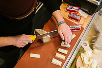 NAPLES, ITALY - 4 JANUARY 2019: Pecorino cheese is cut here at the cold-cut counter of Janarius, a restaurant in Naples, Italy, on January 4th 2019.<br /> <br /> Janarius is a typical Neapolitan gourmet restaurant and shop founded by Francesco Andoli in September 2018 in via Duomo, in front of the Naples's Duomo and treasure of Saint Janarius. Saint Janarius is the patron saint of Naples.
