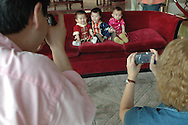 Three adopted kids heave their picture taken on a couch of the White Swan Hotel.