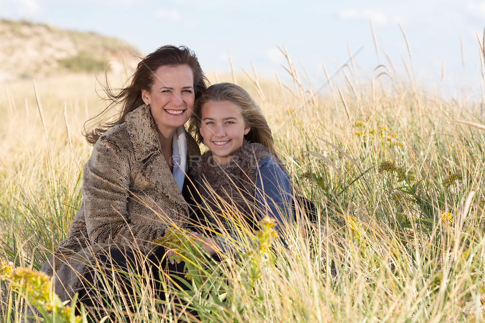 mother and daughter sitting in tall grass at the beach in East Hampton, NY during the Winter