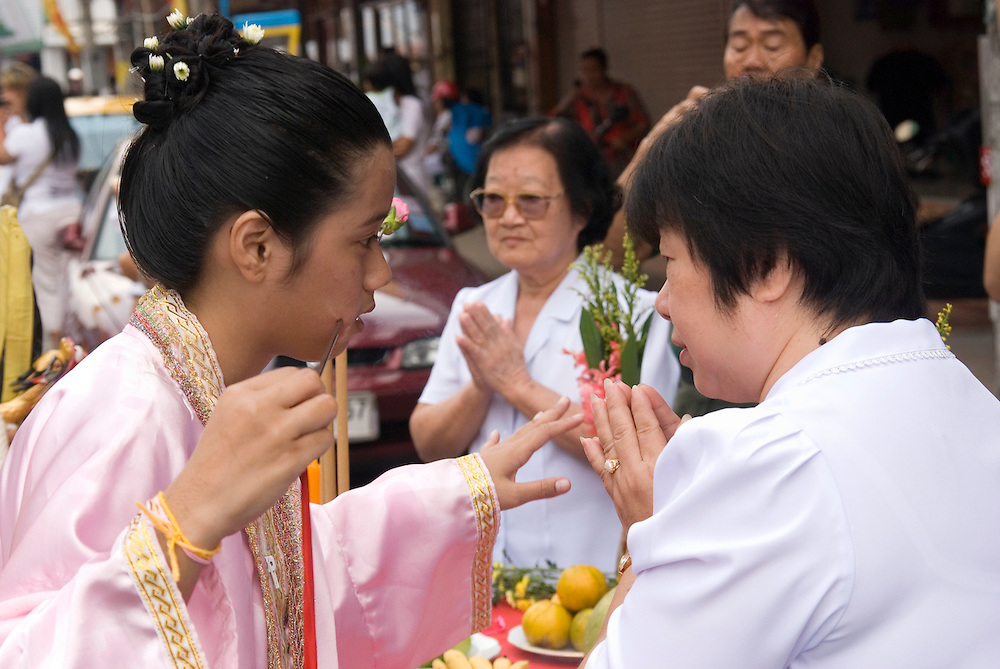 A female medium offers a blessing or advice to a merchant in the Phuket Vegetarian Festival Street Procession, Phuket Town, Thailand.....** The Phuket Vegetarian Festival celebrates the beginning of Taoist Lent, when devout Chinese abstain from eating all meat and other vices.  The festival takes place on the first 9 days of the 9th lunar month of the Chinese calendar.  Everyone dresses in white and shopkeepers set up small alters with offerings of incense, flowers, candles, fruit, and 9 cups of tea to the 9 emperor deities honored by the festival. ....Mediums bring the 9 gods to earth entering a trance state and piercing themselves with all kinds of objects, climbing knife ladders, and walking on hot coals.  The mediums participate in daily processions through town where they stop at the store front alters, drink one of the 9 cups of tea, and offer blessings to the merchants.  The shopkeepers stand in prayer like fashion respecting the mediums that are temporarily possessed by the deity.  The self torture is done to shift evil from individuals to the mediums and bring the community good luck.....Young men carry alters of the deity images though town which culminates at central locations where merchants cover them with huge strands of firecrackers and larger explosives.  The louder and longer blasts are best to drive away evil spirits.  The experience is deafening and engulfs the men and alters in a painful barrage of fire and smoke.  ....Chinese tour groups come to witness since there is no record of this type celebration of Taoist Lent in China.  The festival is believed to have started when a Chinese theatre troupe fell ill for failing to honor the 9 emperor gods of Taoism.  They were quickly cured when they adhered to the 9 day ritual now held each year promoting inner peace, brightness, and proper hygiene.  ..
