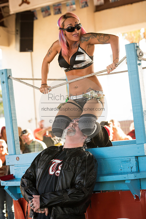 A biker celebrates at Froggies Bar with an exotic dancer during the 74th Annual Daytona Bike Week March 8, 2015 in Daytona Beach, Florida. More than 500,000 bikers and spectators gather for the week long event, the largest motorcycle rally in America.
