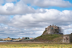Lindisfarne Castle partially clad in scaffolding as it undergoes major restoration works. Holy Island, Northumberland, England, UK<br />