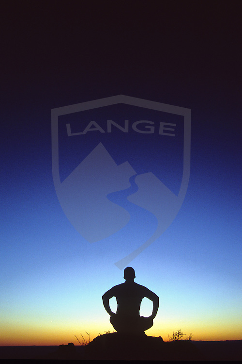 nature scenery landscapes and inspirational people: man silhouetted sitting in yoga lotus position meditating watching the sunset sky, sandia mountains, albuquerque, new mexico