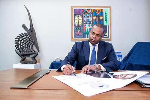 2019 Commencement speaker Kasim Reed seated at a desk surrounded by artwork, signing a poster.
