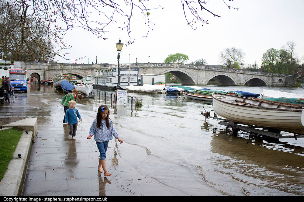 © Licensed to London News Pictures. 30/03/2014. Richmond, UK. Children play along the flooded paths.  The high tide on the River Thames causing flooding in Richmond this afternoon 30th March 2014. Photo credit : Stephen Simpson/LNP