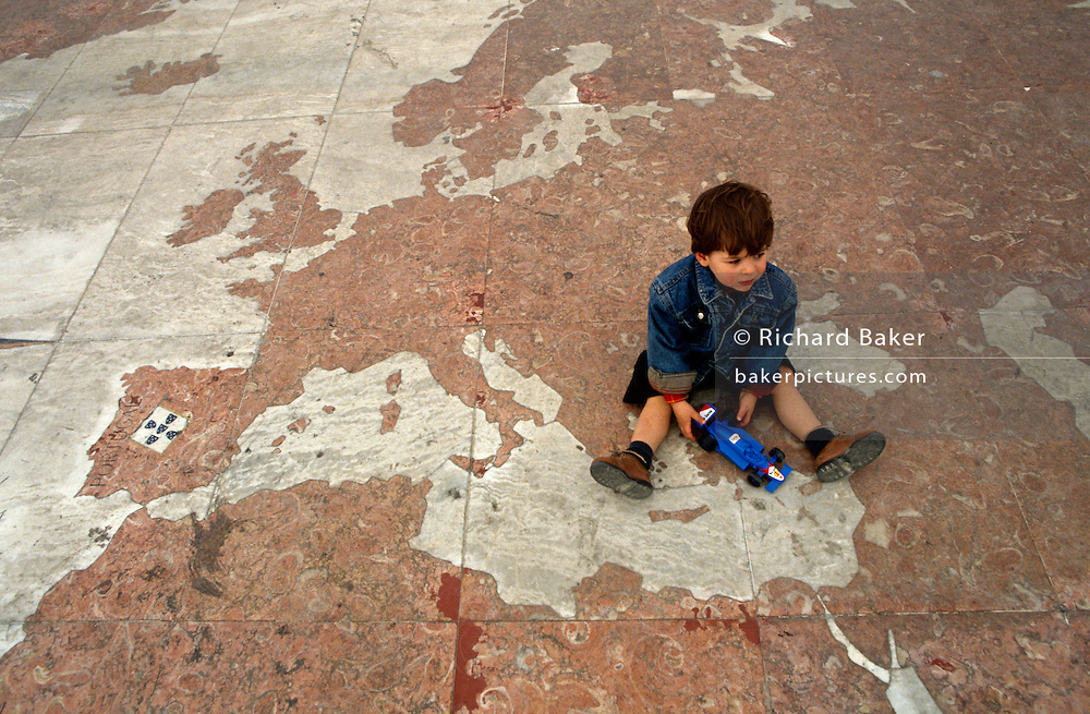 A young boy sits between Europe and Asia on a map laid across the pavement beneath Monument of Discoveries, Lisbon