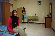 A young Muslim fisherman's wife smiles while sitting on the bed of her rented bungalow on Himmafushi factory island, Maldives.