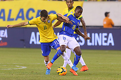 Sep 9, 2014; East Rutherford, NJ, USA; Ecuador defender Juan Cazares (18) and Brazil midfielder Oscar (11)  during the first half at MetLife Stadium.