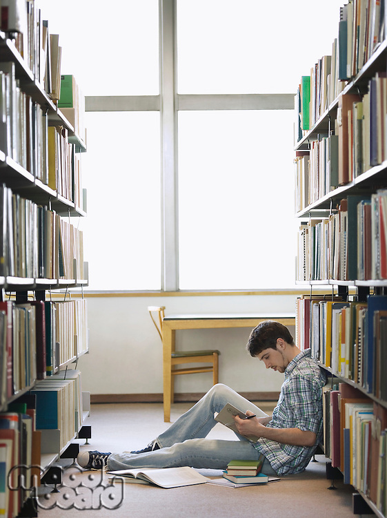 Student reading sitting on floor in library