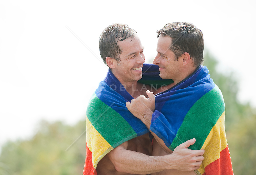 Two Men sharing a rainbow towel outdoors