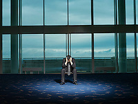 Stressed Businessman sitting alone in room head in hands