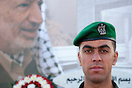 A member of the Palestinian Presidential Guard stands on duty in front of the tomb of Yasser Arafat, here still under construction with a large banner of Arafat covering the construction site. Arafat died in November 2004.