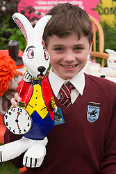 © Licensed to London News Pictures. 19/05/2014. London, England. Jack, 10, from the Holtspur School near Beaconsfield with the White Rabbit which their school designed for the Miracle Gro'wers Discovery and Learning Garden.  Press Day at the RHS Chelsea Flower Show. On Tuesday, 20 May 2014 the flower show will open its doors to the public.  Photo credit: Bettina Strenske/LNP