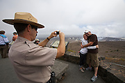 Big Island. Hawai'i Volcanoes National Park. Halema'uma'u Crater in the Kilauea Caldera, spewing sulfur dioxide since 2008. Park Ranger taking souvenir photo of tourists.