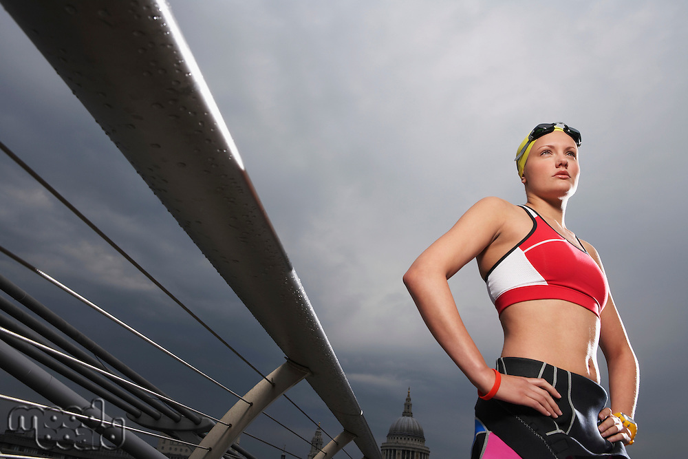 Female swimmer standing on foot bridge low angle view Millennium Bridge London England