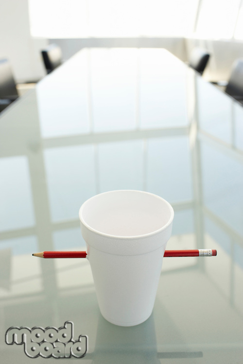 Empty Disposable Cup and Pencil on Conference Table