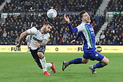 Wigan Athletic midfielder Lee Evans and Derby County midfielder Bradley Johnson challenge for the ball during the EFL Sky Bet Championship match between Derby County and Wigan Athletic at the Pride Park, Derby, England on 5 March 2019.