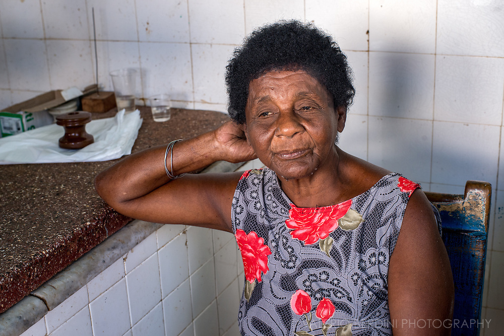 A woman sits inside a butcher shop in Trinidad, Cuba.
