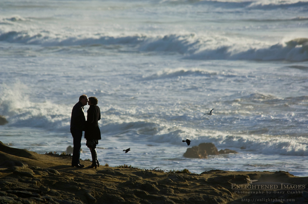 Adult couple kissing in front of ocean, Pescadero State Beach, San Mateo County coast, California