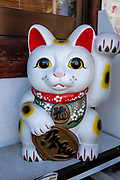 "The maneki-neko, ""beckoning cat"", is a common Japanese figurine (lucky charm or talisman) which is often believed to bring good luck to the owner. In common interpretation, the left paw raised attracts customers (as displayed in businesses); and/or the right paw raised invites good fortune and money (as displayed at home). Often made of ceramic or plastic, the figurine depicts a cat (traditionally a calico Japanese Bobtail) beckoning with an upright paw, and is usually displayed at the entrance of shops, restaurants, pachinko parlors and other businesses. Some of the sculptures have electric or battery-powered paws. Common colors are white, black, gold and sometimes red. The beckoning cat probably originated in Tokyo (or possibly Kyoto). Earliest records of Maneki-neko appear in the Buko nenpyo's (a chronology of Edo) entry dated 1852. Differing from Western body language, the Japanese beckoning gesture is made by holding up the hand, palm down, and repeatedly folding the fingers down and back, thus explaining the cat's appearance. Photo from Kumano Nachi Taisha shrine, Nachikatsuura, Kii Mountains, Japan."