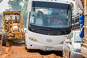 09 MARCH 2013 - ALONG HIGHWAY 13, LAOS:  A tourist bus tries to navigate road construction on Highway 13 near the Lao capital of Vientiane. The paving of Highway 13 from Vientiane to near the Chinese border has changed the way of life in rural Laos. Villagers near Luang Prabang used to have to take unreliable boats that took three hours round trip to get from the homes to the tourist center of Luang Prabang, now they take a 40 minute round trip bus ride. North of Luang Prabang, paving the highway has been an opportunity for China to use Laos as a transshipping point. Chinese merchandise now goes through Laos to Thailand where it's put on Thai trains and taken to the deep water port east of Bangkok. The Chinese have also expanded their economic empire into Laos. Chinese hotels and businesses are common in northern Laos and in some cities, like Oudomxay, are now up to 40% percent. As the roads are paved, more people move away from their traditional homes in the mountains of Laos and crowd the side of the road living off tourists' and truck drivers.    PHOTO BY JACK KURTZ