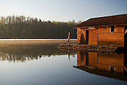Woman does a head stand beside a lake in early morning light next to the boathouse.