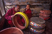 A novice monk assists his master in making drums at Semtokha Monastery.