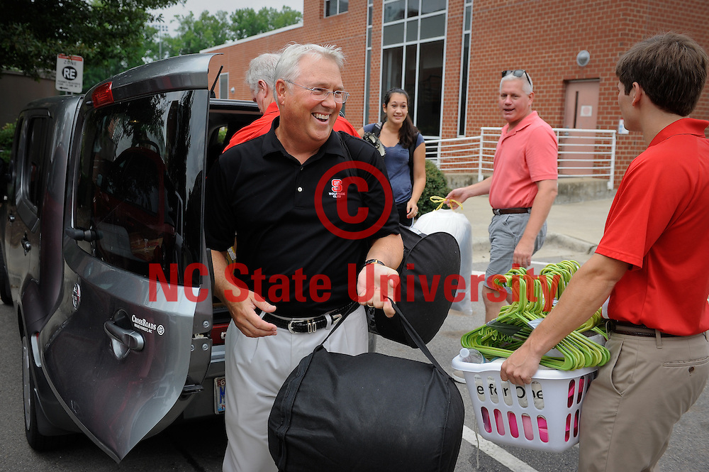 Chancellor Woodson digs right in and grabs some bags during move in. Photo by Marc Hall