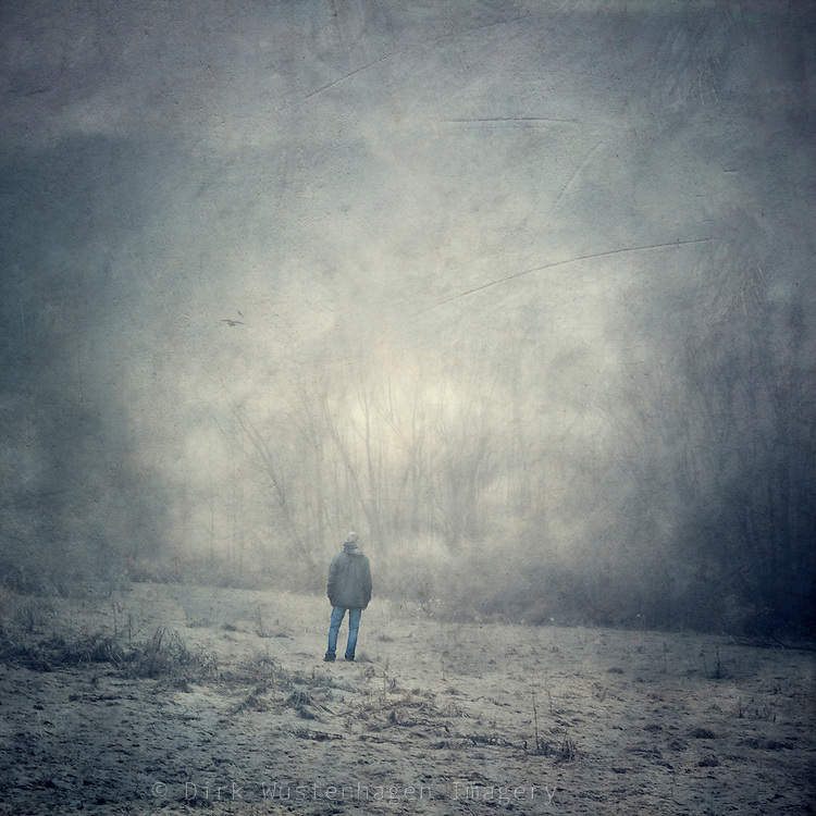 Man standing on a frosted pasture
