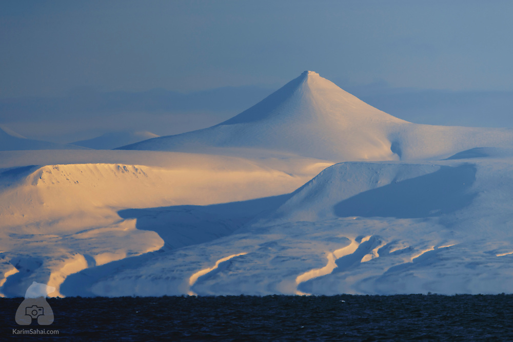 After many months of Polar Night, the sun has finally reappeared in the skies of Svalbard. The Kjeglefjella mountain range, the conical 'Vesuv' peak, the deep polar blues and the golden polar light create a breathtaking vista.